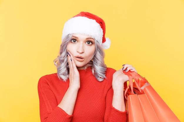 Santa meisje in hoed grote zakken met cadeautjes geïsoleerd in gele kamer te houden.