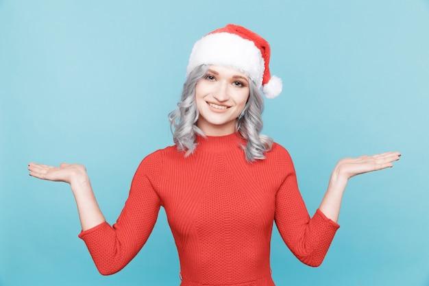 Santa meisje in rode jurk en hoed staande geïsoleerd.