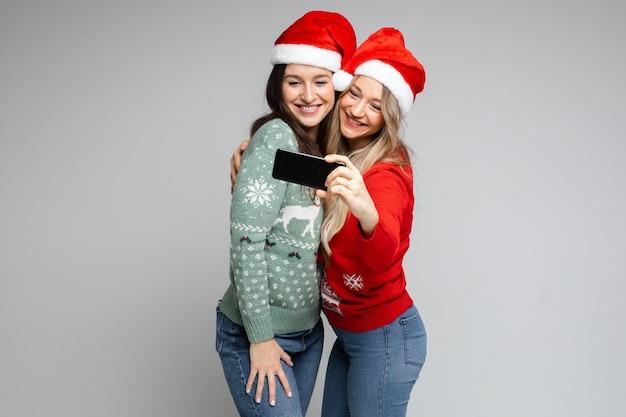 Santa meisjes vrienden in rode hoeden poseren met telefoon voor feestelijke selfie op grijze achtergrond met kopie ruimte