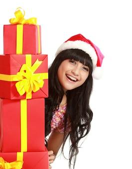 Santa vrouw winkelen met vele geschenken dragen kerstmuts glimlachend gelukkig. mooi vrouwelijk model geïsoleerd.