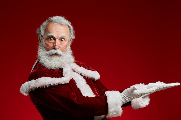 Santa wijzend op rode achtergrond