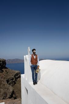 Santorini oia griekenland, jonge man bij het zwembad met uitzicht op de oceaan caldera van santorini tijdens vakantie