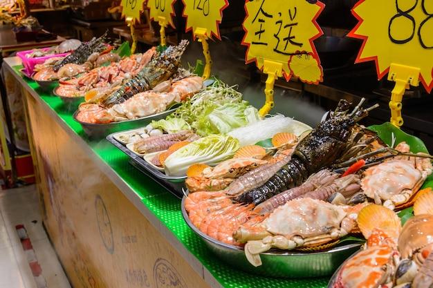 Sanya, hainan/china - 7 januari 2020: chinees straatvoedsel. straathandel. chinese soorten verse zeevruchten op een aziatische vismarkt in sanya, provincie hainan, china. opschrift: naam eten.