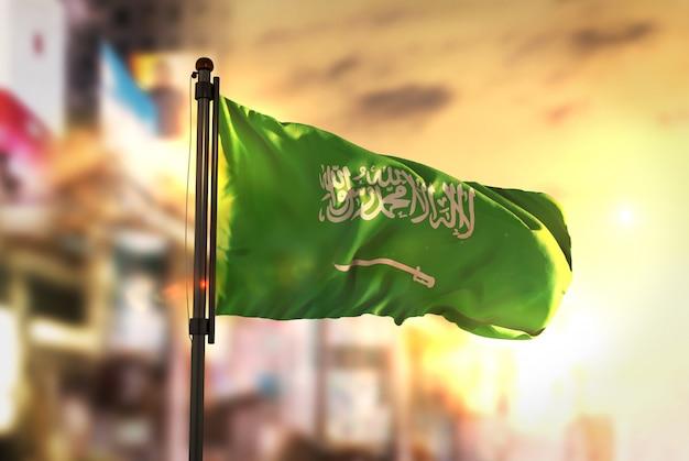 Saoedi-arabië vlag tegen stad wazige achtergrond bij zonsopgang achtergrondverlichting