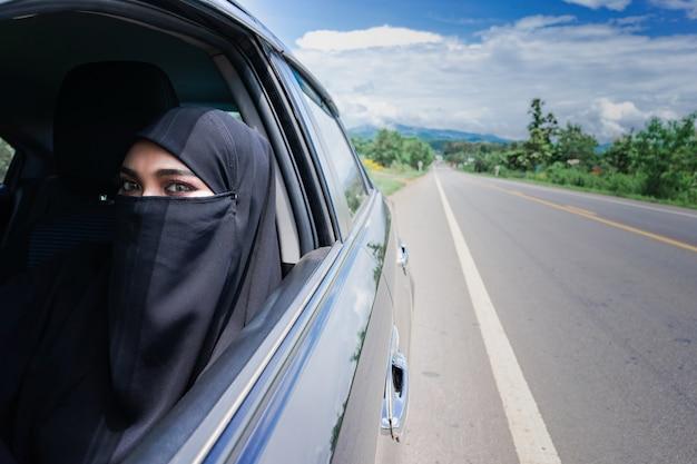 Saoedi-arabische vrouw besturen van een auto op de weg. moslimvrouw stuurprogramma concept