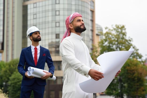 Saoedische zakenman die het bouwplan doorloopt met zijn architect die op wacht