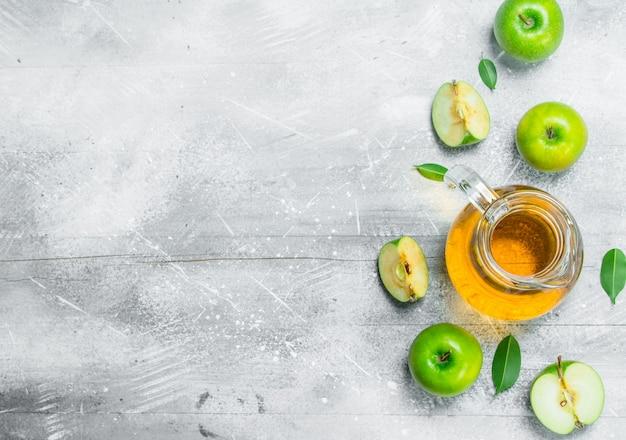 Sap en verse appels in een glazen pot met plakjes appels. op wit rustiek oppervlak.