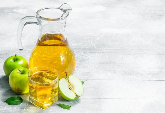 Sap en verse appels in een glazen pot met plakjes appels. op witte rustieke achtergrond.