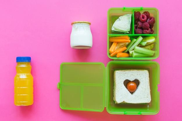 Sap en yoghurt dichtbij lunchbox met voedsel