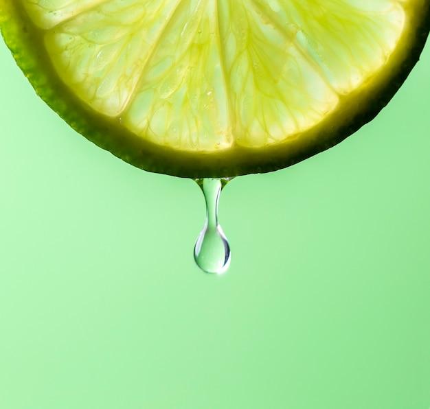 Sap in de vorm van een druppel die voortvloeit uit een schijfje limoen, op groene achtergrond.
