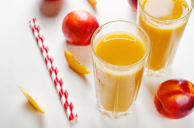 Sap van perziken en nectarines met pulp met vers fruit op een witte achtergrond.