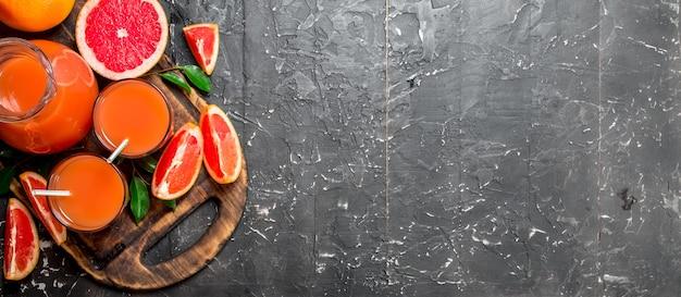 Sap van rijpe grapefruit in een kruik op snijplank op rustieke tafel