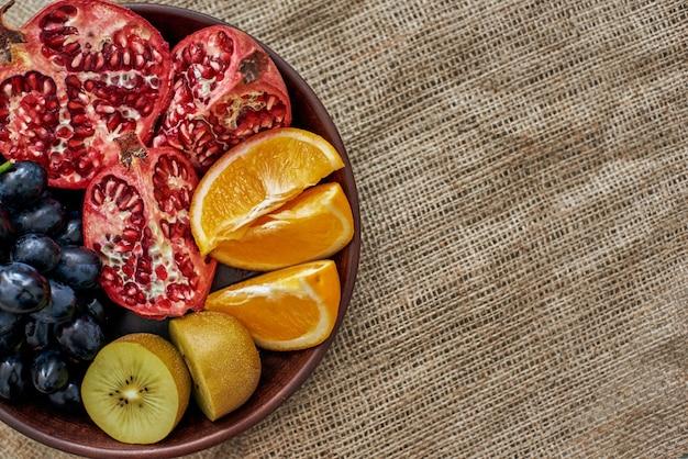 Sappig fruit. bovenaanzicht van een vol bord sappig, gesneden fruit op een houten bord met druiven, sinaasappel, granaatappel en kiwi op de jutedoek