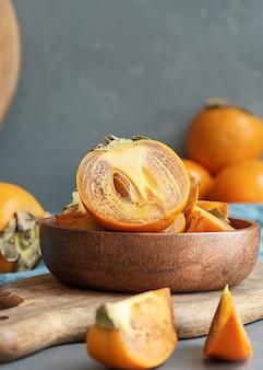 Sappig gesneden persimmon in een houten beker met kopieën van de ruimte.