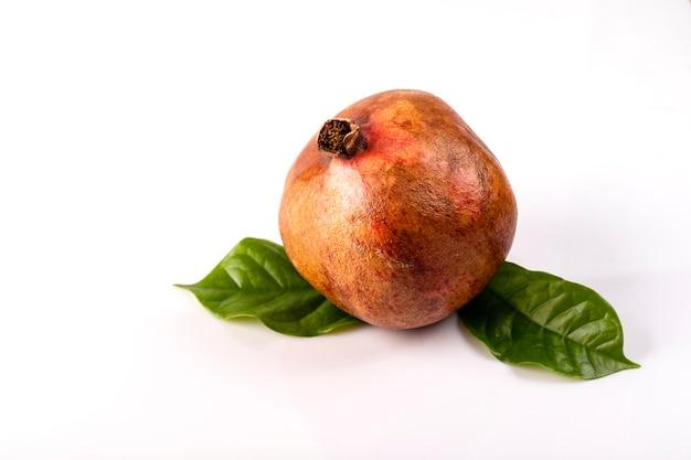 Sappig granaatappelfruit met bladeren op de lijst op een witte achtergrond.