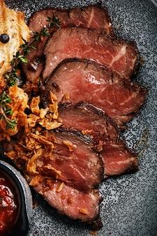 Sappig rosbief met ciabatta in tomatensaus wordt prachtig in plakjes gesneden en op borden gelegd