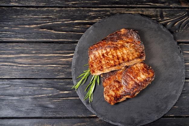 Sappig stuk gebakken vlees ligt op een stenen plaat tegen een zwarte houten tafel