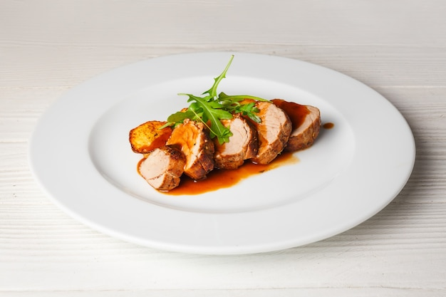 Sappig stukje gegrild vlees met gebakken aardappelen en rucola op een witte plaat.