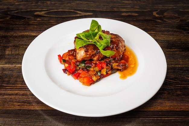 Sappig stukje vlees met gestoofde groenten en basilicum en roomsaus op een witte plaat.