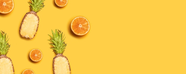 Sappig tropisch fruit op een gele achtergrond: sinaasappelen, kokosnoten, citroenen, ananassen.