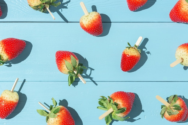 Sappige aardbeien op een stokje op een blauwe tafel met scherpe schaduwen.