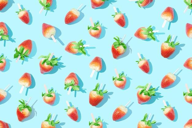 Sappige aardbeien op een stokje op een helderblauwe achtergrond met scherpe schaduwen.