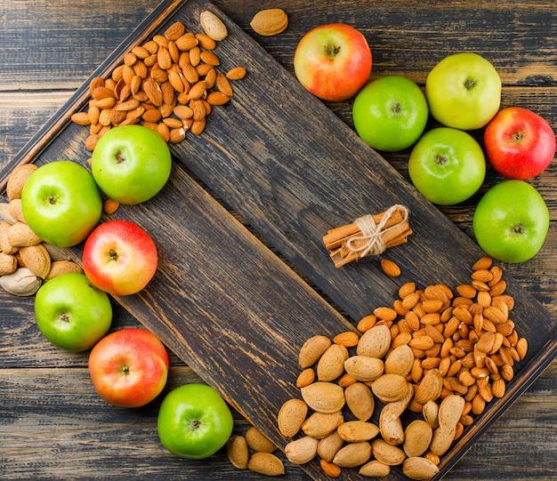 Sappige appels met kaneelstokjes, stapel van amandelen op een houten bord en houten achtergrond