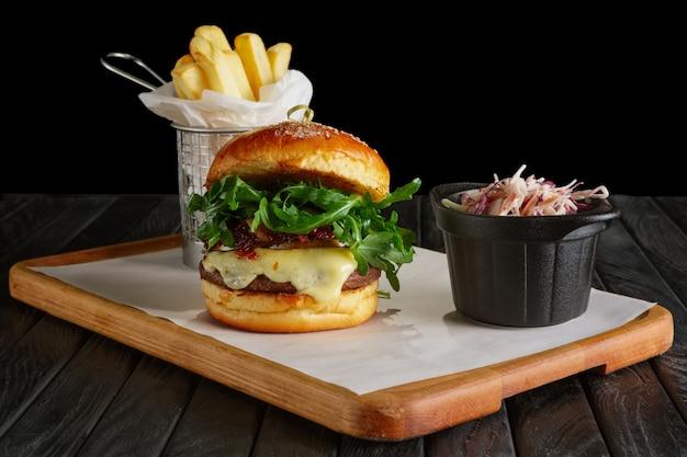 Sappige biefhamburger met bosbessensaus, gesmolten kaas, rucola geserveerd met gefrituurde aardappel en rode kool
