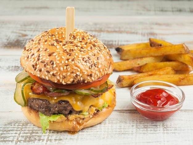 Sappige burger met rundvlees, bacon, kaas, komkommer en tomaat