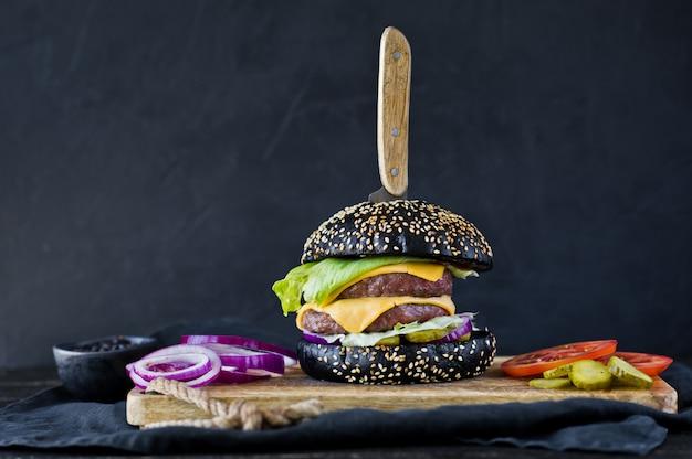 Sappige cheeseburger op een houten snijplank.