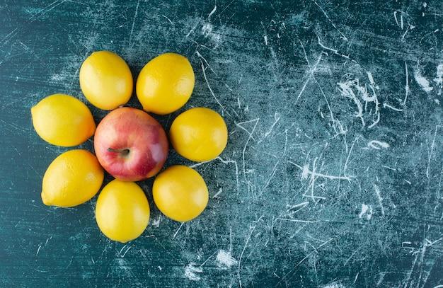 Sappige citroenen en rode appel op marmeren tafel.