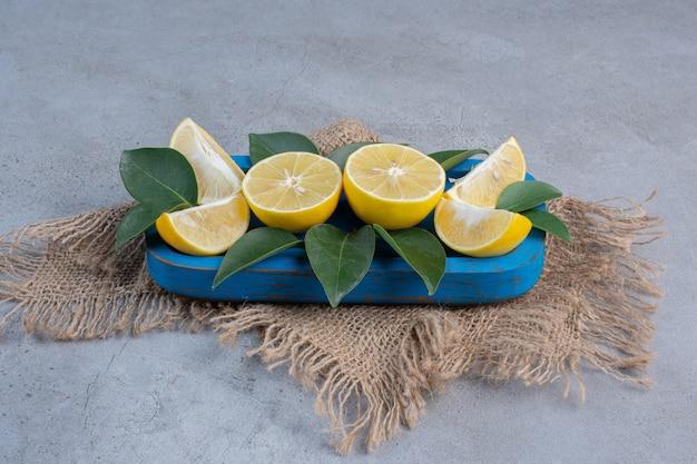 Sappige citroenplakken en bladeren op een blauwe schotel op marmeren achtergrond.