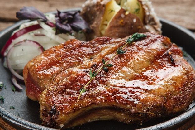 Sappige gegrilde beaf staak geserveerd met gebakken aardappel en uienringen, close-up weergave. amerikaanse keuken.