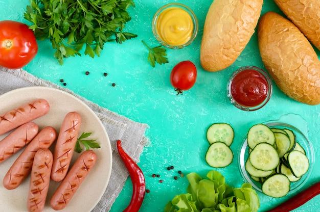 Sappige gegrilde worstjes, verse groenten, groenten en knapperige broodjes. bovenaanzicht. ingrediënten voor hotdogs. plat liggen.