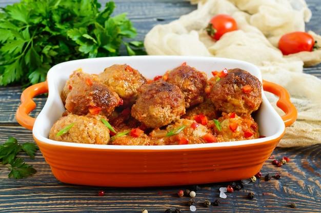 Sappige gehaktballen in een pikante tomatensaus op een houten tafel. gerecht van gehakt.