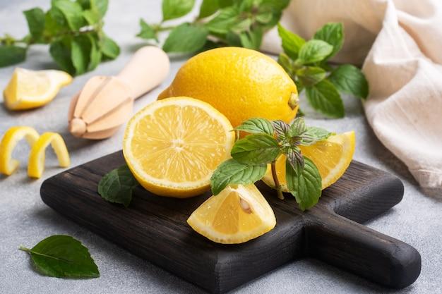 Sappige gele citroenen heel en gesneden met verse muntblaadjes