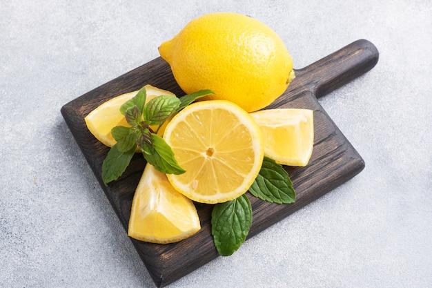 Sappige gele citroenen in hun geheel en gesneden met verse muntblaadjes