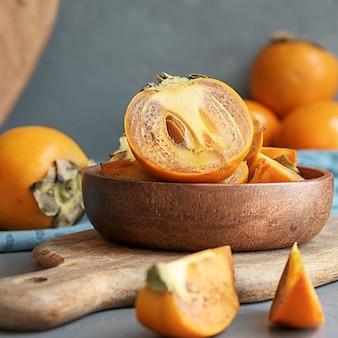 Sappige gesneden persimmon in een houten kopje op een betonnen achtergrond.