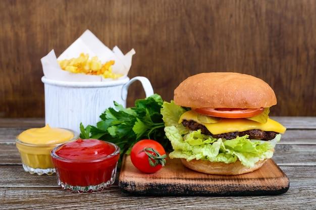 Sappige hamburger, frietjes en sauzen op een houten achtergrond. fast food. straatvoedsel.