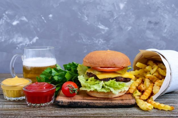 Sappige hamburger, frietjes, sauzen, bier op een houten achtergrond.