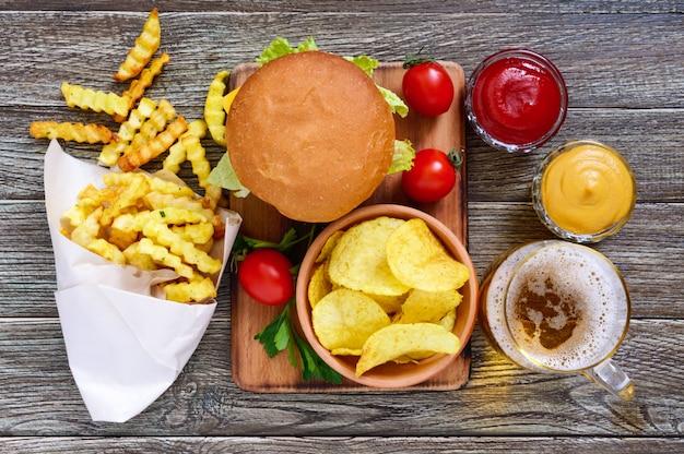 Sappige hamburger, frietjes, sauzen, chips, bier op een houten achtergrond. het bovenaanzicht