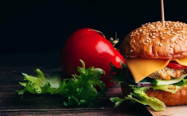 Sappige hamburger met vlees, kaas, sla, tomaat en ui