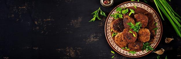 Sappige heerlijke vleeskoteletten op een donkere lijst. russische keuken. bovenaanzicht