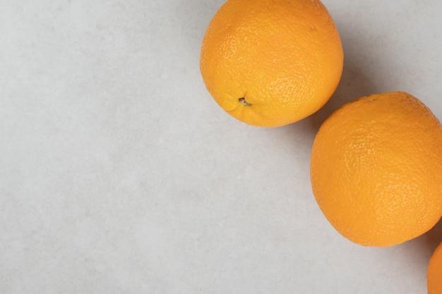 Sappige hele sinaasappels op grijs oppervlak
