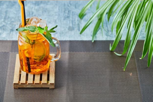 Sappige limonade met stro en munt op het plantoppervlak