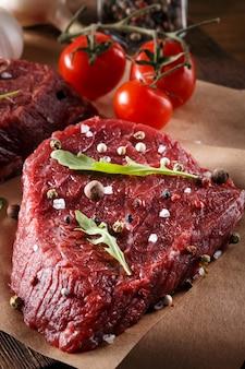 Sappige malse rauwe magere runderlapjes vlees liggen op een vel ovenpapier in de keuken met verse kruiden en specerijen klaar om te worden gekookt voor het diner