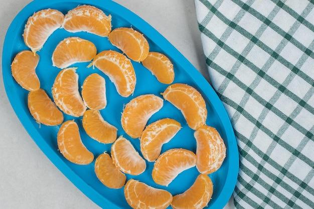 Sappige mandarijnsegmenten op blauw bord
