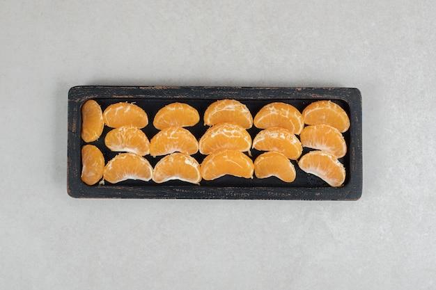 Sappige mandarijnsegmenten op zwarte plaat