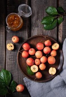Sappige mini-appels in een plaat met een potje jam op een oude houten