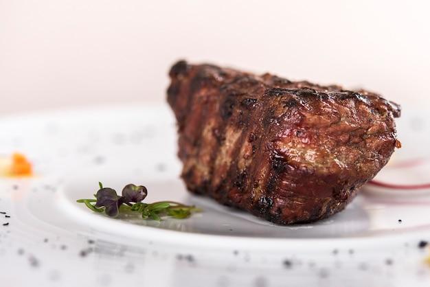 Sappige ossenhaas biefstuk, geserveerd met boter met kruiden, versierd met radijs